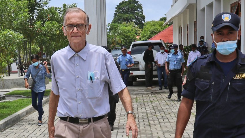 A police officer escorts Richard Daschbach, left, a former missionary from Pennsylvania, U.S. upon his arrival for a trial at a courthouse in Oecusse, East Timor, Tuesday, Feb. 23, 2021.