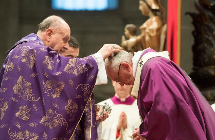 Cardinal Angelo Comastri, left, places the ashes on the head of Pope Francis during the Ash Wednesday mass, in St. Peter's Basilica at the Vatican, Wednesday, Feb. 10, 2016. (Credit: L'osservatore Romano / Pool Photo via AP.)