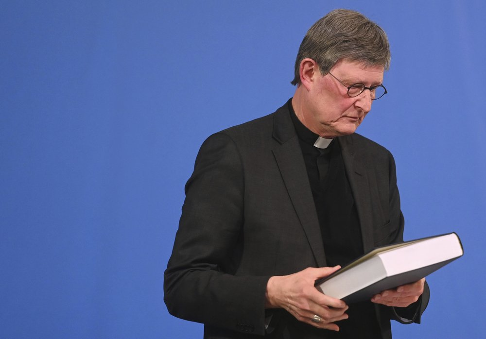 Cologne's archbishop Cardinal Rainer Maria Woelki holds a report on abuse by clergy he had receives during a news conference in Cologne, Germany, Thursday, March 18, 2021. Faced with accusations of trying to cover up sexual violence in Germany's most powerful Roman Catholic diocese, the archbishop of Cologne publishes the independent investigation. (Ina Fassbender / Pool via AP)