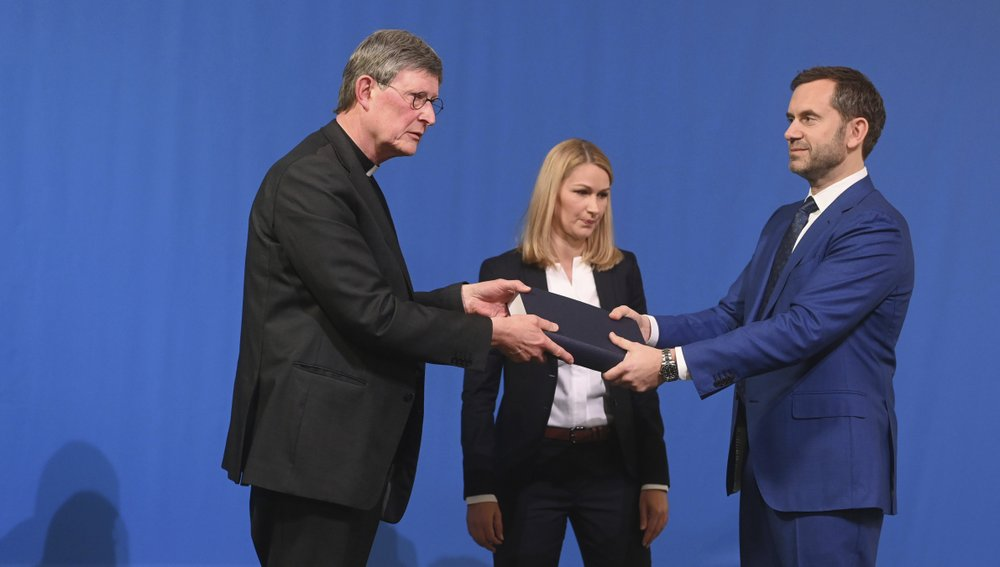 Lawyer Kerstin Stirner, center, looks on as Bjoern Gercke, right, an attorney mandated by the Church, hands over a report on abuse by clergy to Cologne's archbishop Cardinal Rainer Maria Woelki, left, during a news conference in Cologne, Germany, Thursday, March 18, 2021. Faced with accusations of trying to cover up sexual violence in Germany's most powerful Roman Catholic diocese, the archbishop of Cologne publishes the independent investigation. (Ina Fassbender / Pool via AP)