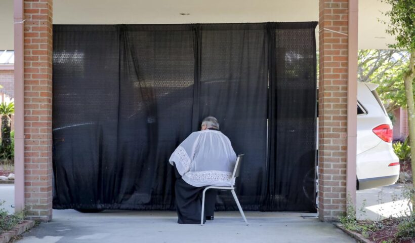 The Rev. Pat Wattigny of St. Luke the Evangelist Catholic Church in Slidell holds a drive-up confessional Wednesday, April 1, 2020, one of the changes the church has made due to the coronavirus pandemic.