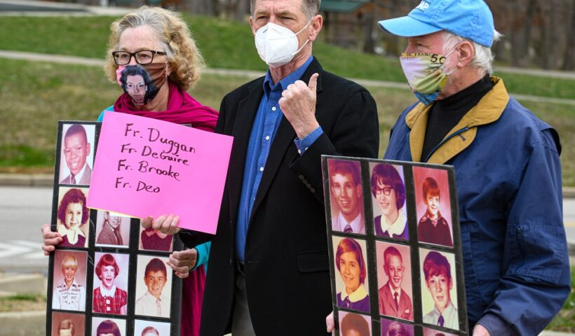 While David Chohessy, middle, addresses the media, Judy Jones, on left, and Steven Spaner hold up poster boards containing two dozen grade school photographs of known victims of abuse by Catholic priests. Jones is SNAP Midwest coordinator while Spaner is the coordinator for Australia Clohessy, the former national director of Survivors Network of those Abused by Priests, spoke Wednesday morning near the Catholic Chancery to ask Bishop Shawn McKnight to take more steps concerning the list of credibly accused clergy. Julie Smith/News Tribune