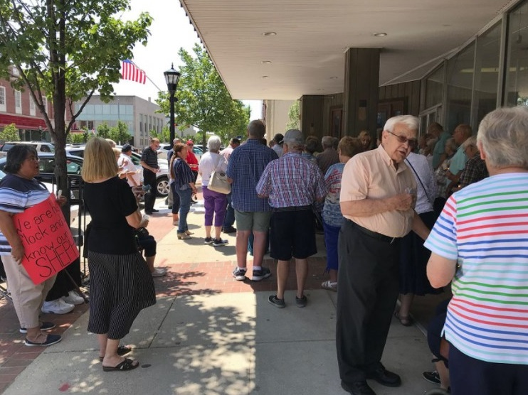 Demonstrators gather in front of the downtown Bay City law office of attorney Matthew L. Reyes on the afternoon of July 24, 2019, to show their support for the Rev. Dennis H. Kucharczyk.
