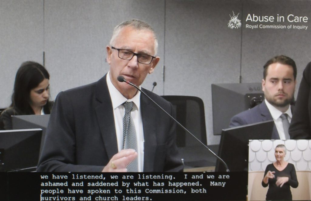 Cardinal John Dew of Wellington, New Zealand, is pictured in a screenshot speaking March 22, 2021, at a hearing of the New Zealand Royal Commission on Abuse in Care in Auckland. The royal commission directed that no attendees at public hearings should wear religious attire or uniforms, as that could be triggering for abuse survivors. (Credit: CNS screenshot/NZ Catholic.)