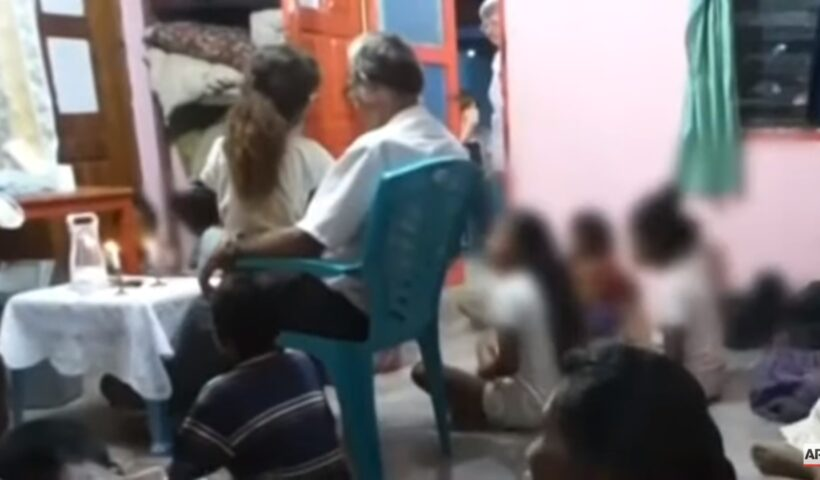 Richard Daschbach with victim at prayer meeting with other children. Screen shot from Associated Press video.