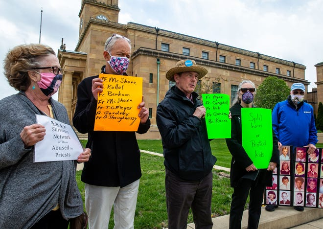 """David Clohessy, center, holds up a sign with the names of five priests accused of abuse as members of the Survivors Network of those Abused by Priests, SNAP, gather to urge Bishop Thomas John Paprocki to include the names on the diocese's list of """"credibly accused""""; priests during a protest at the Cathedral of the Immaculate Conception in Springfield, Ill., Wednesday, April 21, 2021. [Justin L. Fowler / The State Journal-Register]"""