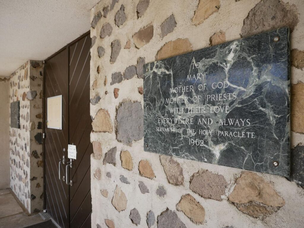 A Servants of the Paraclete plaque from 1962 is posted outside the door of Mary, Mother of Priests Catholic Church in Jemez Springs. Matt Dahlseid / The New Mexican