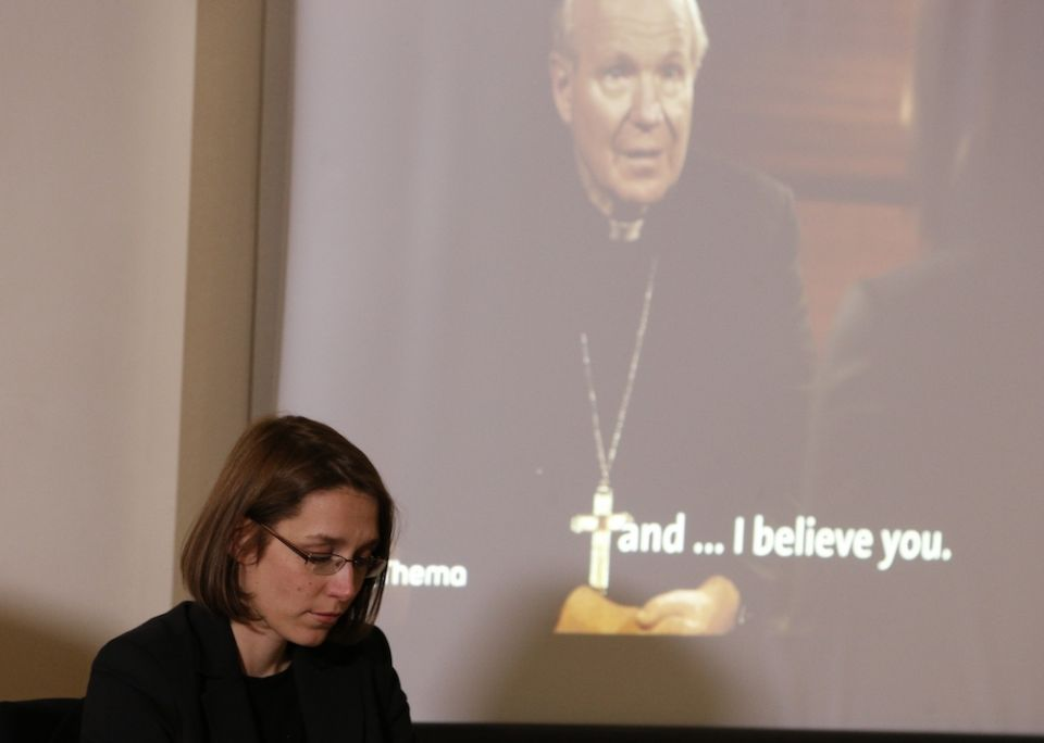 Doris Reisinger, an abuse survivor and former nun, is pictured as a video of her talking with Cardinal Christoph Schonborn of Vienna plays in the background during a news conference in Rome Feb. 19, 2019. (CNS/Paul Haring)