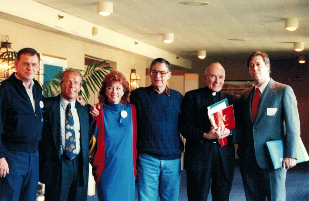 Jeanne Miller with speakers at the first VOCAL / Linkup Conference in Arlington Heights IL on October 16-18, 1992. Left to right: Tom Doyle, Jeff Anderson, Jeanne Miller, Richard Sipe, Fr. Andrew Greeley, and Jason Berry.