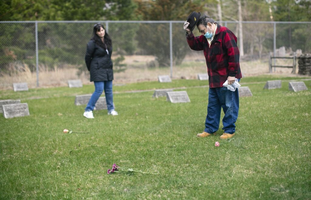 After spreading Bobby's ashes, Chuck bows his dead and takes his hat off during a moment of silence as his friend Joanna Kruse watches. Charles 'Chuck' Carroll is spreading his brother Bobby's ashes at the cemetery on the grounds of the New Lisbon Developmental Center, an institution for people with developmental disabilities. Chuck and Bobby were wrongly placed there as kids in the 1950s and were sexually assaulted for years. Saturday, April 10, 2021. Pemberton, N.J. Aristide Economopoulos | NJ Advance Media