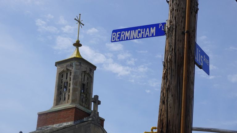 A street sign in front of St. Aidan Roman Catholic Church in Williston Park honors its former pastor, the Rev. Charles Bermingham, after whom the street was renamed. Bermingham, however, landed on a list of clerics accused of sexually abusing minors. Some are calling for the signs to be removed. Credit: Debbie Egan-Chin