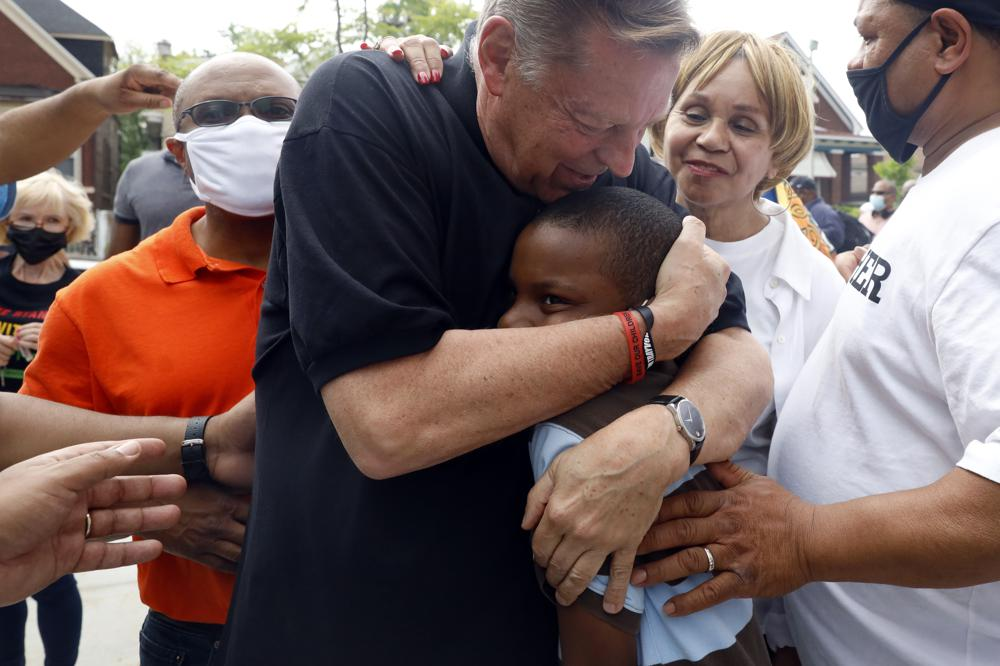 Father Michael Pfleger embraces Jordan-Amman Isiah West-Williams, 9, who was baptized by Father Pfleger, following his reinstatement by Archdiocese of Chicago, Monday, May 24, 2021, in front of St. Sabina Catholic Church in the Auburn Gresham neighborhood in Chicago. (AP Photo/Shafkat Anowar)