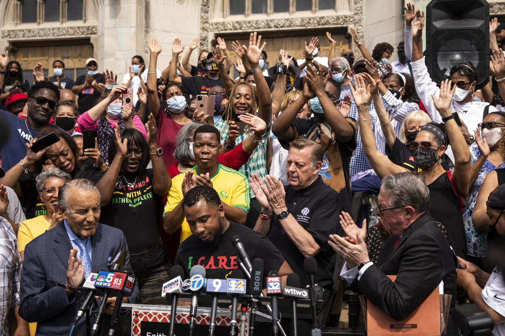 Father Michael Pfleger stands among supporters before a news conference outside St. Sabina Church, after the Archdiocese of Chicago announced that Pfleger will return to his role at senior pastor at at the Auburn Gresham church, Monday afternoon, May 24, 2021. The archdiocese cleared him to return after an internal probe into decades-old allegations of sexual abuse against minors. (Ashlee Rezin Garcia/Chicago Sun-Times via AP)