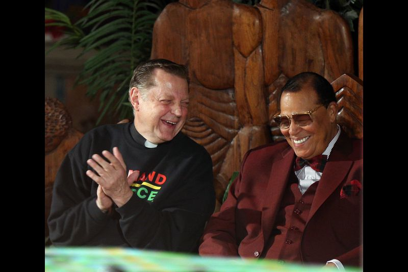 By TERRENCE ANTONIO JAMES / CHICAGO TRIBUNE The Rev. Michael Pfleger, left, shares a laugh with Nation of Islam leader Louis Farrakhan as Farrakhan prepares to speak to people gathered at St. Sabina Church in Chicago on May 9, 2019. Farrakhan was invited to speak after he was banned from the social media platforms Facebook and Instagram. (Terrence Antonio James / Chicago Tribune)