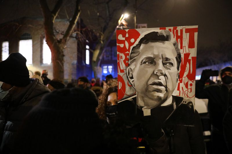 By CHRIS SWEDA / CHICAGO TRIBUNE Sandra Jackson displays an image of the Rev. Michael Pfleger as supporters rally Jan. 8, 2021, in his defense outside St. Sabina Church in Chicago's Auburn Gresham community. (Chris Sweda / Chicago Tribune)