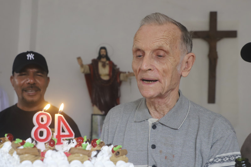 Now-defrocked Catholic priest Richard Daschbach, centre, is presented a cake during his 84th birthday in Dili in January. CREDIT:AP