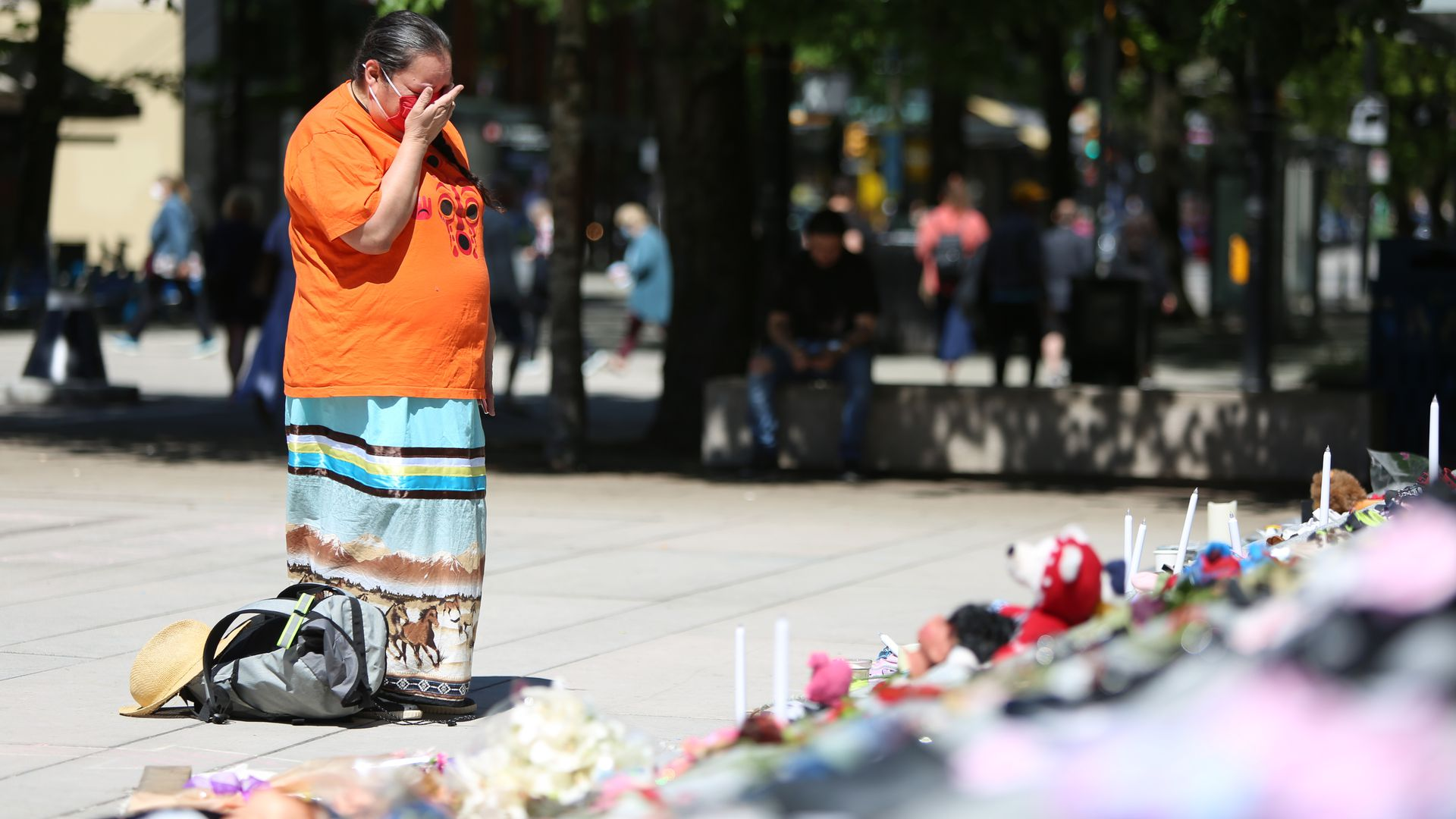 A woman mourns beside 215 pairs of children's shoes outside Vancouver Art Gallery during a memorial in Vancouver, British Columbia, Canada, Saturday, after a mass grave of Indigenous children was found. Photo: Mert Alper Dervis/Anadolu Agency via Getty Images