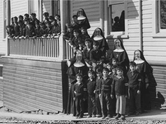 Catholic church officials with Indigenous children outside the St. Paul's Indian Residential School in North Vancouver. PHOTO BY INDIAN RESIDENTIAL SCHOOL HISTORY AND DIALOGUE CENTRE / PNG
