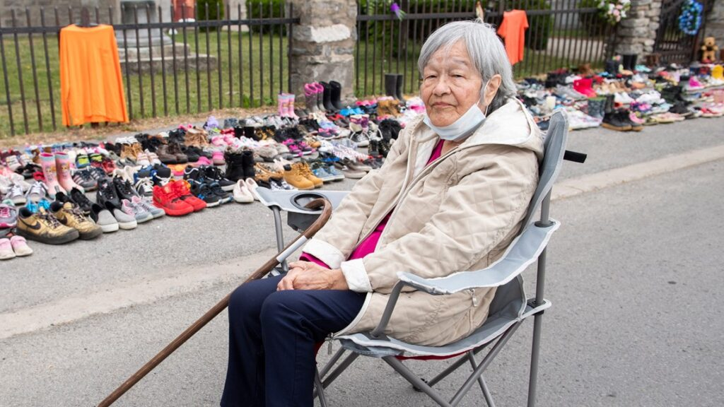 Residential school survivor Betty Deer sits next to children's shoes, placed there as a tribute to the victims of the residential school system outside St. Francis Xavier Church in Kahnawake, Quebec, Sunday, May 30, 2021.  Associated Press
