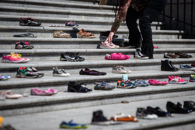 A woman places one of 215 pairs of children's shoes on the steps of the Vancouver Art Gallery as a memorial to the 215 children whose remains have been found buried at the site of a former residential school in Kamloops, in Vancouver, on May 28, 2021.  Darryl Dyck / Canadian Press