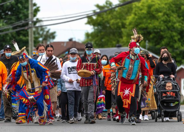 Members of the community of the Kahnawake Mohawk Territory, Quebec march through the town on May 30, 2021, to commemorate the news that a mass grave of 215 Indigenous children were found at the Kamloops Residential School in British Columbia.  Peter McCabe / Agence France-Presse
