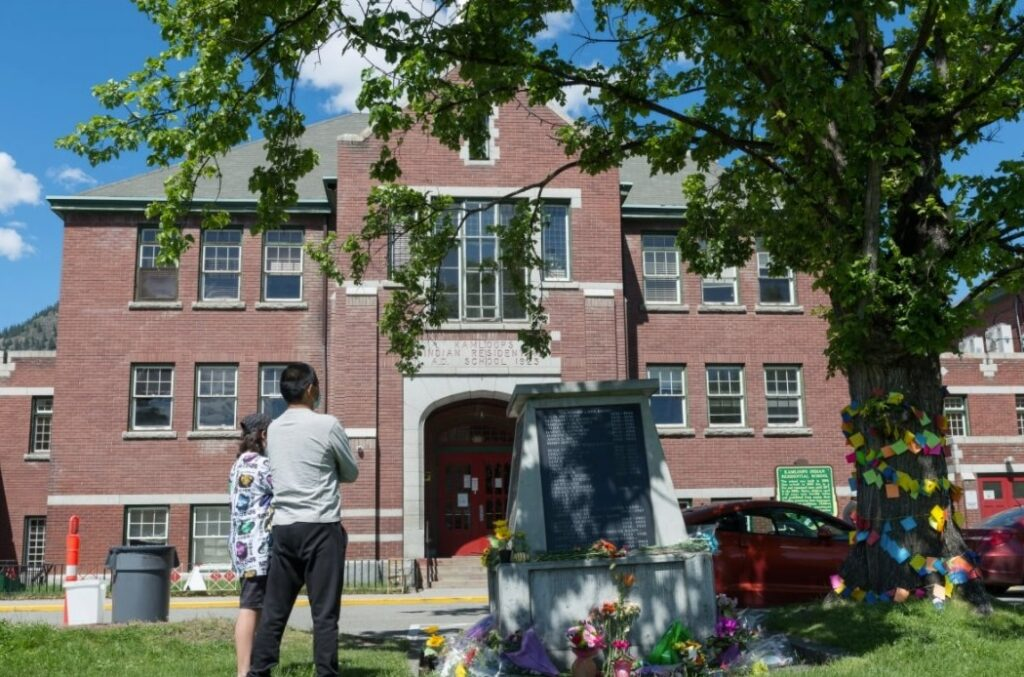The remains were discovered during a search of the grounds of the former residential school, pictured above. Efforts are underway to recover the remains of the children. In this photo, a man stands with his son in front of a monument to the survivors of the former Kamloops Indian Residential School on May 29. (Dennis Owen / Reuters)