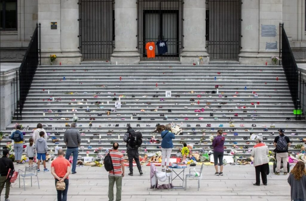 Communities across Canada have been mourning and honouring 215 residential school children since last Thursday, when Tk'emlúps te Secwépemc First Nation said their remains were found at the site of a former residential school in Kamloops, B.C., using ground-penetrating radar. On May 31, people pay their respects at a growing memorial in Vancouver. (Ben Nelms / CBC)