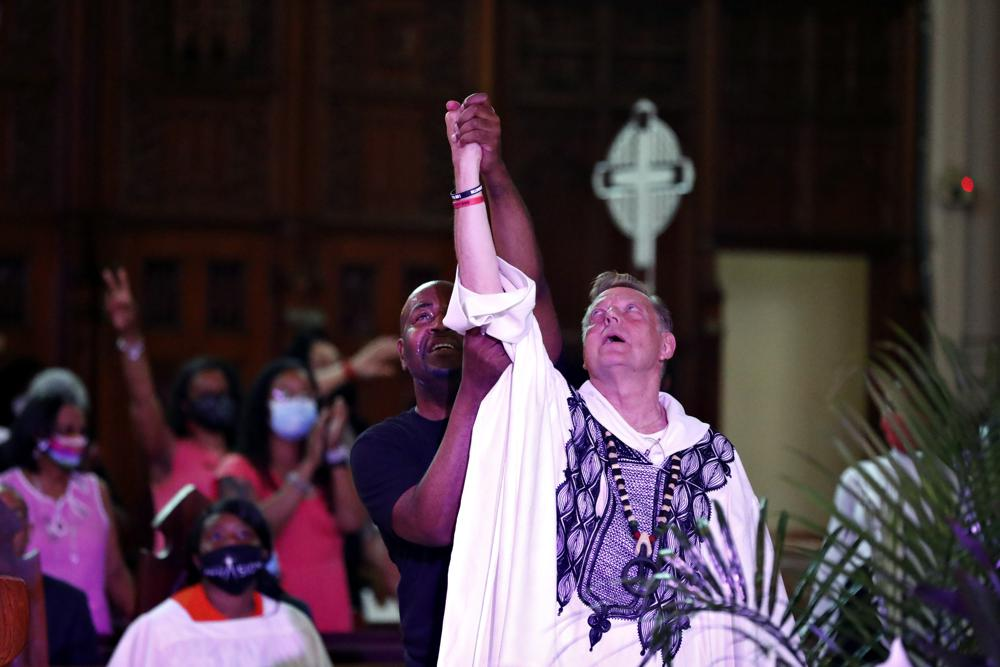 A parishioner raises Rev. Michael Pfleger's arm as he conducts his first Sunday church service as a senior pastor at St. Sabina Catholic Church following his reinstatement by Archdiocese of Chicago after decades-old sexual abuse allegations against minors, Sunday, June 6, 2021, in the Auburn Gresham neighborhood in Chicago. (AP Photo/Shafkat Anowar)