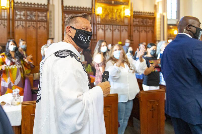 By VASHON JORDAN JR. / CHICAGO TRIBUNE The Rev. Michael Pfleger is greeted by parishioners as he enters the sanctuary at St. Sabina Church to lead the Sunday morning service on June 6, 2021. (Vashon Jordan Jr. / Chicago Tribune)