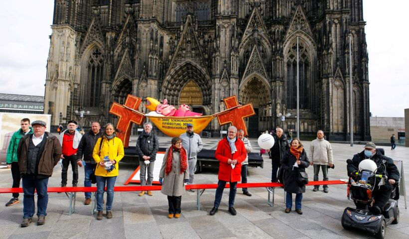 """Demonstrators pose for a picture next to a carnival float showing an unnamed bishop from the 2019 """"Rosenmontag"""" (Rose Monday) parade of Duesseldorf placed in front of the Cologne Cathedral by activists of the Giordano Bruno Foundation to protest against sexual abuse by Catholic priests in Cologne, Germany, March 18, 2021. Float reads """"11 years of brutal honest reconnaissance of sexual abuse"""". REUTERS/Thilo Schmuelgen"""