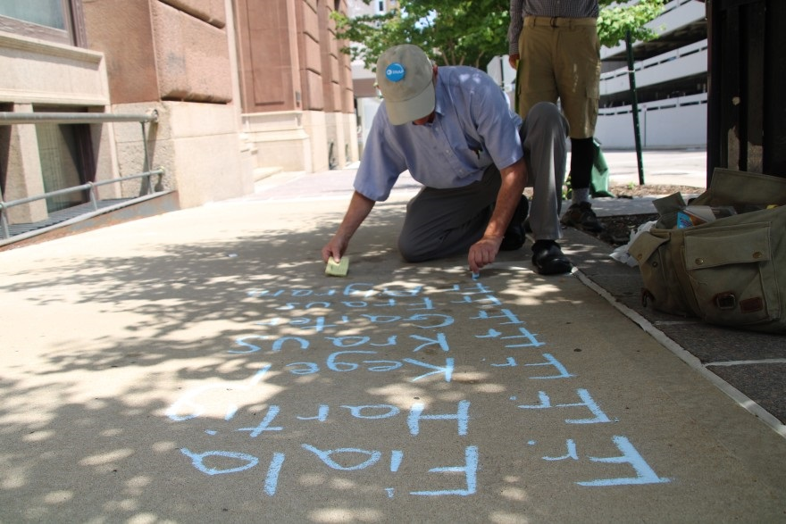David Clohessy, former executive director of SNAP, the Survivors Network of those Abused by Priests, writes the names of priests left out of the Kansas City diocese's list in front of their headquarters.