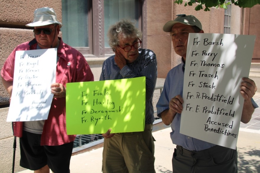 Longtime SNAP members, David Biersmith, Tom White, and David Clohessy hold up signs listing the accused priests' names.