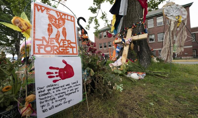 Signs are pictured at a memorial outside the Residential School in Kamloops, British Columbia., Sunday, June, 13, 2021. The remains of 215 children were discovered buried near the former Kamloops Indian Residential School earlier this month. (Jonathan Hayward/The Canadian Press via AP)