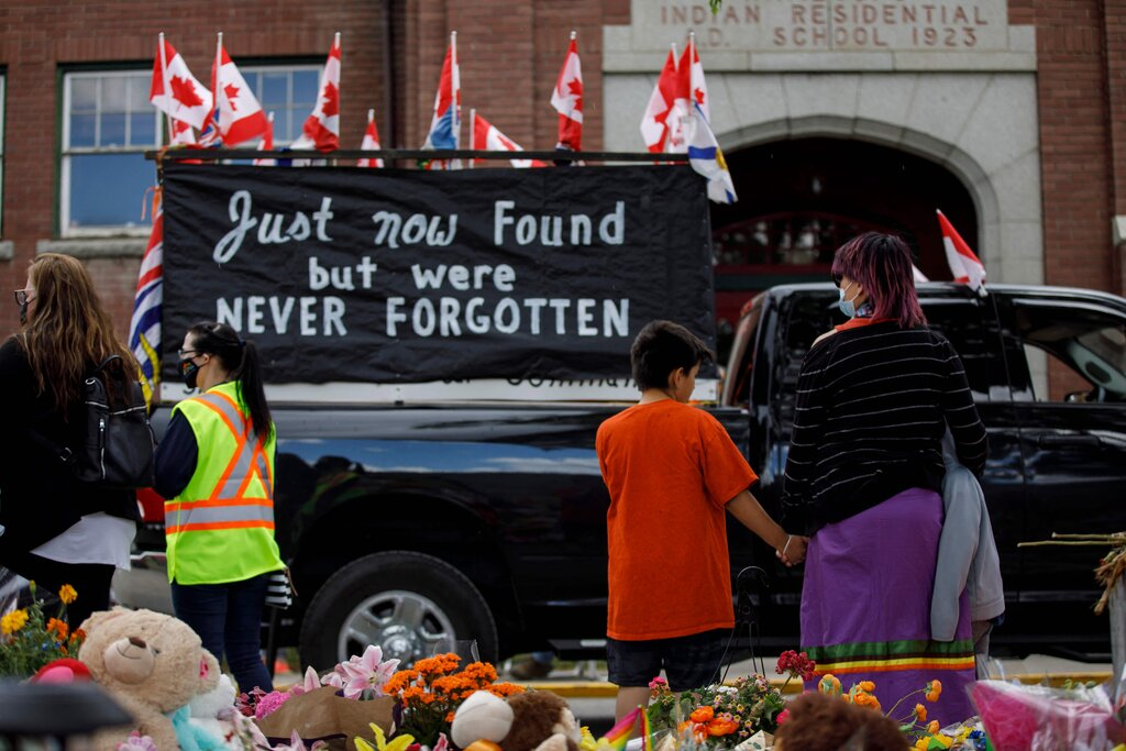 A convoy of vehicles driving past the Kamloops Indian Residential School after the remains of more than 200 children were found buried there in unmarked graves earlier this month.Credit...Cole Burston/Agence France-Presse — Getty Images