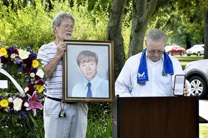 """Carl Croteau Jr., (left), and his brother Joe stand as Joe plays """"Danny Boy"""" during a graveside memorial service at Hillcrest Cemetery in Springfield for their little brother Danny, 13-year-old altar boy authorities determined was killed by his parish priest in 1972. (Don Treeger / The Republican)"""