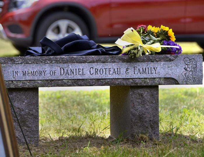 Flowers sit on a memorial bench near the grave of Danny Croteau in Hillcrest Cemetery during a graveside memorial service for the 13-year-old altar boy authorities determined was killed by his parish priest in 1972. (Don Treeger / The Republican) 6/28/2021