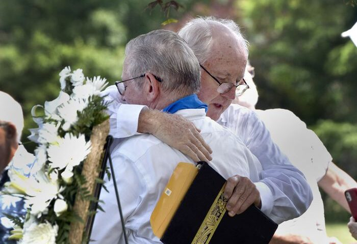 Joe Croteau, left, hugs Retired priest Rev. James Scahill after Scahill spoke at held a graveside memorial service for Joe's little brother Danny, the 13-year-old altar boy authorities determined was killed by his parish priest in 1972. (Don Treeger / The Republican) 6/28/2021