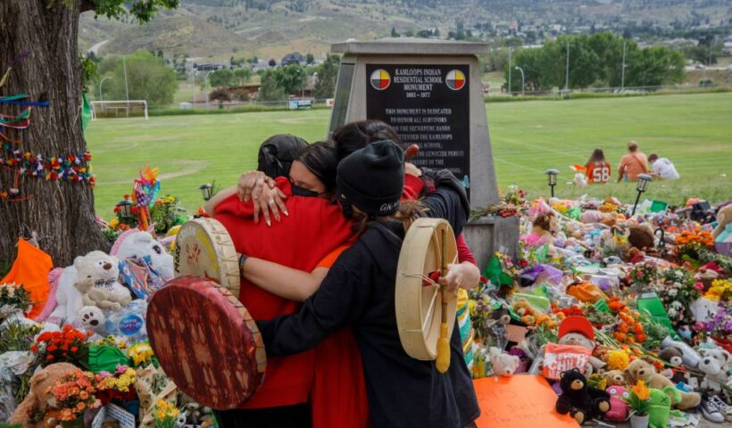 """People from Mosakahiken Cree Nation hug in front of a makeshift memorial at the former Kamloops Indian Residential School to honour the 215 children whose remains have been discovered buried near the facility, in Kamloops, British Columbia, Canada, on June 4, 2021. - Canadian Prime Minister Justin Trudeau on June 4 urged the Catholic Church to """"take responsibility"""" and release records on indigenous residential schools under its direction, after the discovery of remains of 215 children in unmarked graves. (Photo by Cole Burston / AFP)"""
