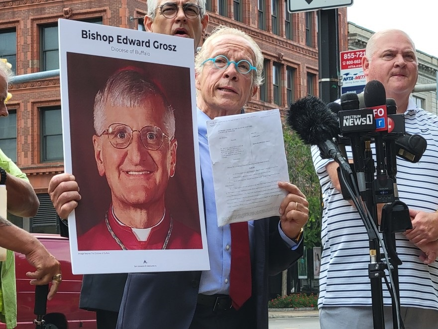 Attorney Jeff Anderson holds up a photo of retired Buffalo Auxiliary Bishop Edward Grosz and a copy of a Child Victims Lawsuit July 14, 2021, outside the Catholic Diocese of Buffalo headquarters.