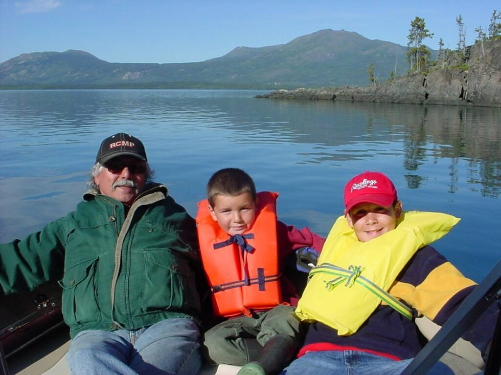 Richard Hardy, left, a residential school survivor and his grandsons McKenzie Barney and Dakota Barney take a boat trip on Atlin Lake, B.C. Photo courtesy of Richard Hardy