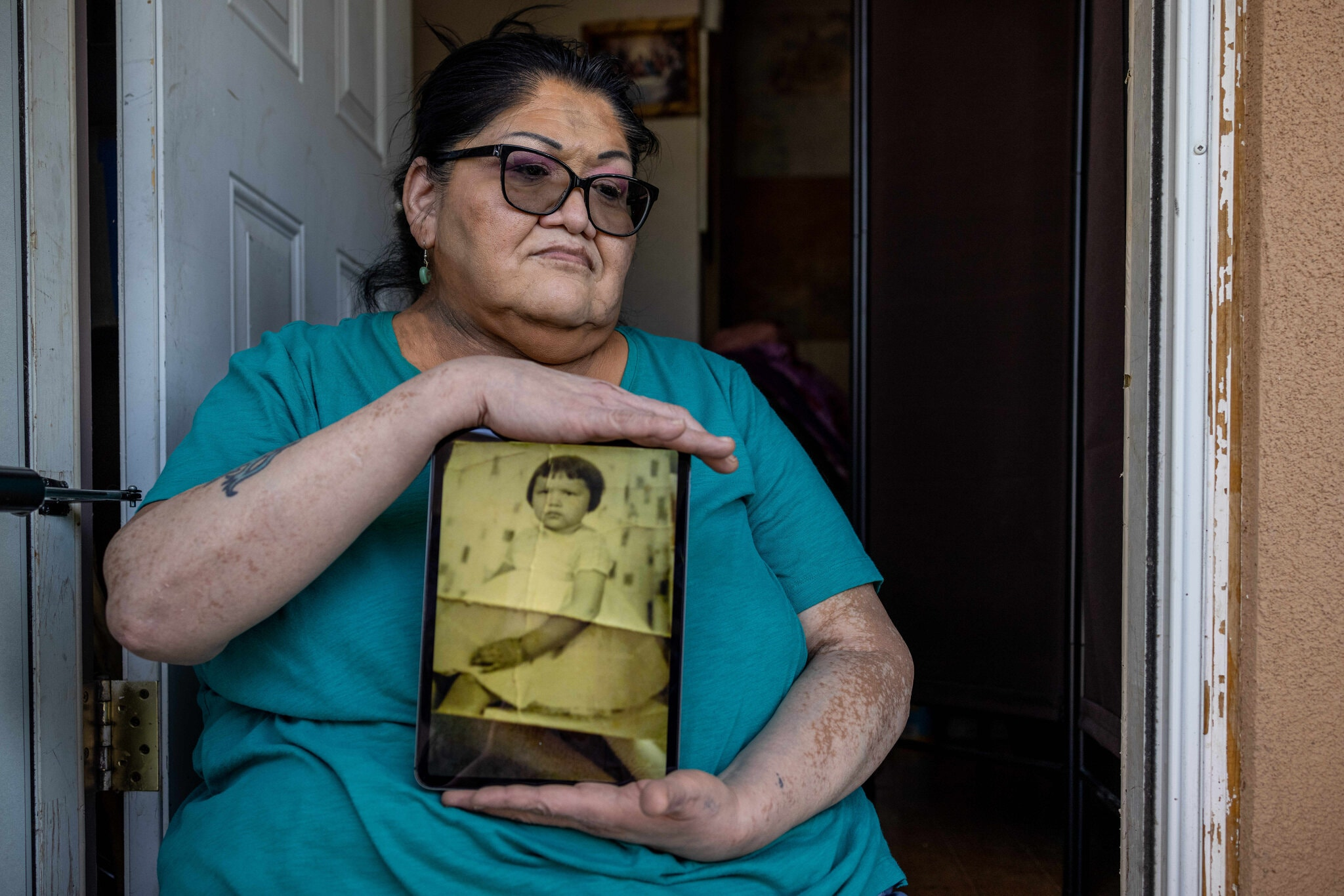 [Jacqueline Frost, 60, holds a photo showing how she was forced to adopt the look and attire of a white girl. She said she was beaten by a Ute aunt who served as a matron at a federal boarding school designed to assimilate Native children.Credit...Sharon Chischilly for The New York Times]