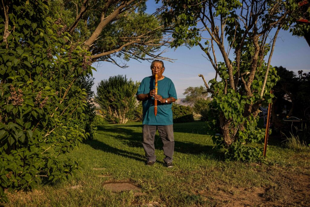 [Norman Lopez, 78, playing a flute outside of his home. He said a boarding school teacher in Colorado smashed his hand-carved flute and threw it in the trash.Credit...Sharon Chischilly for The New York Times]