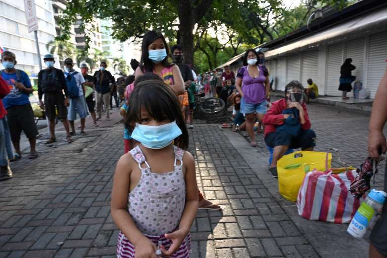 Street dwellers including children queue for free food distributed by the Society of the Divine Word in Manila. The pandemic has brought an increase in the sexual abuse of children in the Philippines. (Photo: AFP)