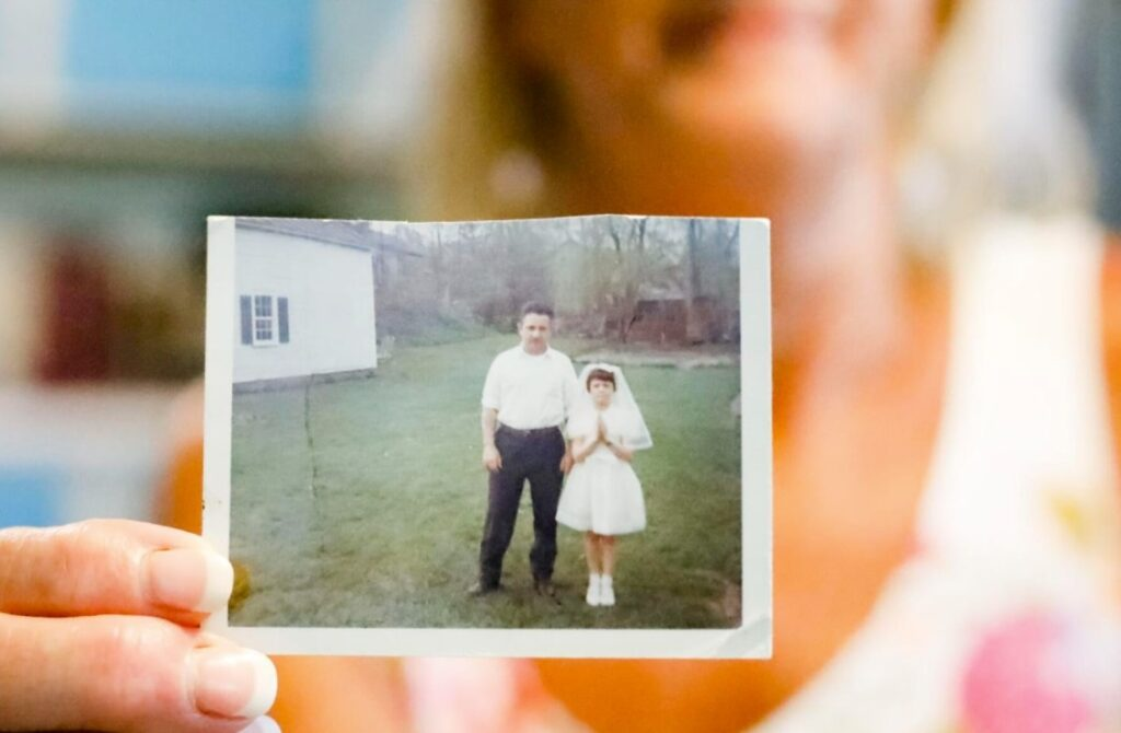 """Sheri Biasin, 61, holds a photograph from 1967 of herself at age 7 with her father at her childhood home in West Stockbridge, on the day of her first Communion. Just hours after the photograph was taken, """"that little girl's life changed forever,"""" Biasin said. That day, Biasin was subjected to the first of what would become a yearslong pattern of sexual abuse by the priest who delivered her Communion.  Stephanie Zollshan - Berkshire Eagle"""