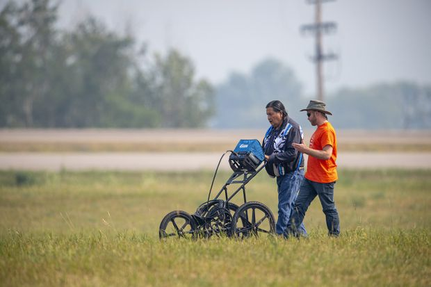 SNC Lavalin engineer Evan Ulmer, right, and Alvin Baptiste use equipment to conduct a search of the grounds at the site of a former Residential School in Delmas, Sask., on July 17, 2021. LIAM RICHARDS/THE CANADIAN PRESS