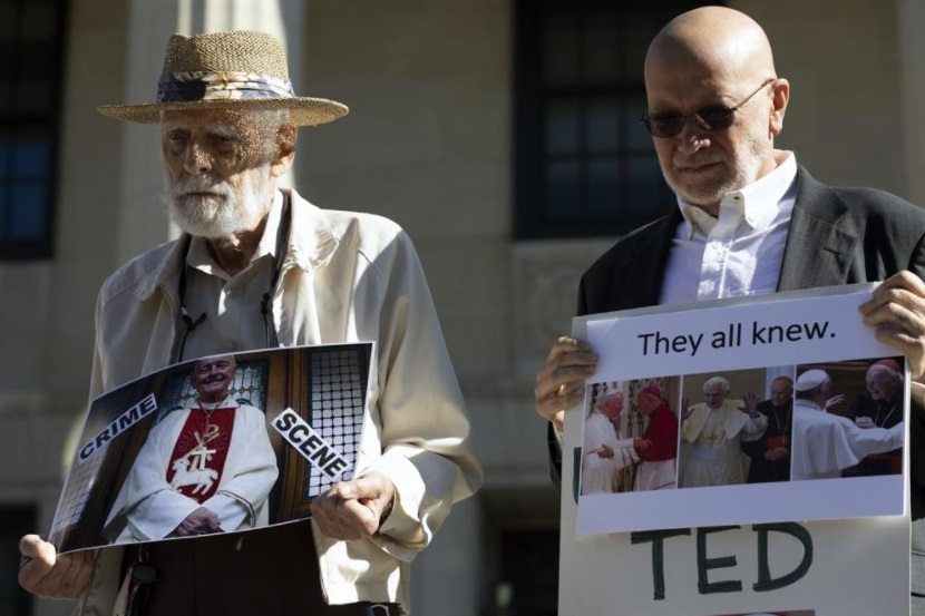 Stephen Sheehan, left, and Skip Shea hold signs during a news conference outside Dedham District Court following the arraignment of former Cardinal Theodore McCarrick, Friday, Sept. 3, 2021, in Dedham, Mass. McCarrick has pleaded not guilty to sexually assaulting a 16-year-old boy during a wedding reception in Massachusetts nearly 50 years ago. (AP Photo / Michael Dwyer)