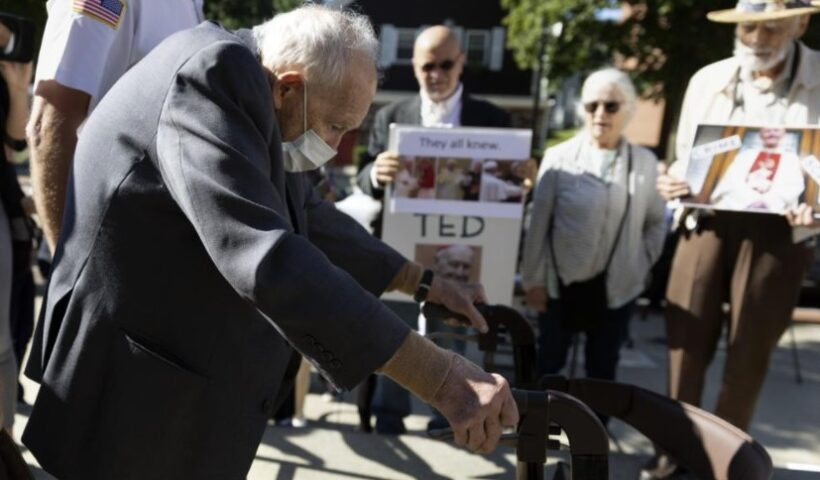 Demonstrators [Skip Shea, Susan Renehan, and Stephen Sheehan] watch as former Cardinal Theodore McCarrick leaves Dedham District Court after his arraignment, Friday, Sept. 3, 2021, in Dedham, Mass. McCarrick has pleaded not guilty to sexually assaulting a 16-year-old boy during a wedding reception in Massachusetts nearly 50 years ago. (AP Photo / Michael Dwyer)