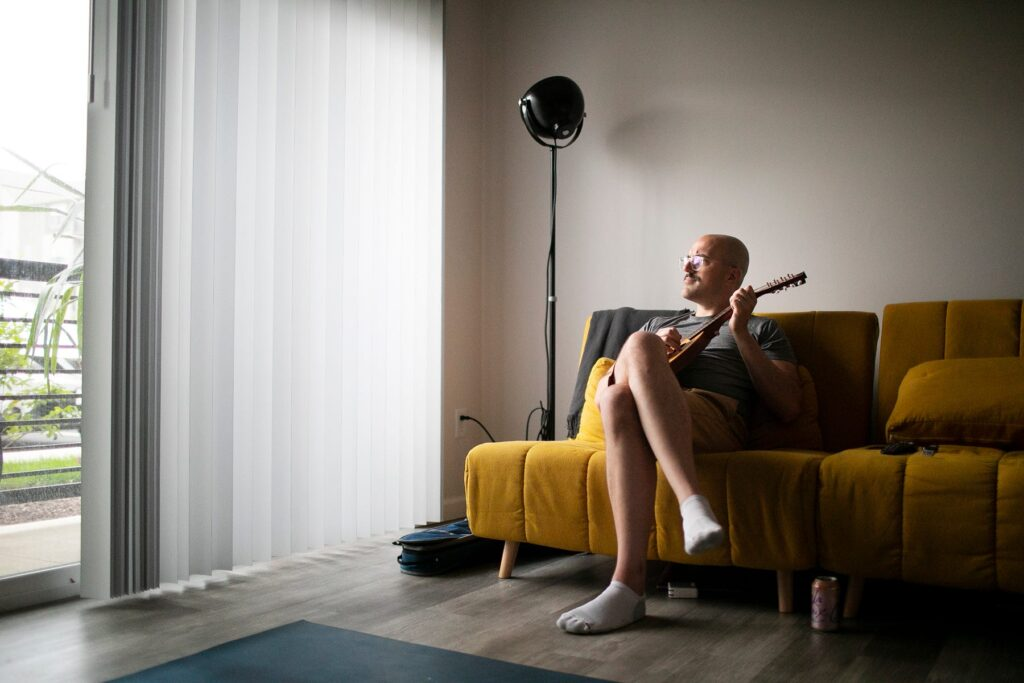 Chris Graham plays a mandolin at home in Westerville after an intense Eye Movement Desensitization and Reprocessing (EMDR) psychotherapy session. Therapy has helped Graham recover repressed memories of being raped by a Columbus priest when he was 14 years old. COURTNEY HERGESHEIMER/COLUMBUS DISPATCH